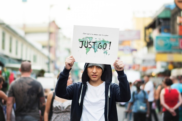 Jeune mec asiatique avec une pancarte just go Photo Premium