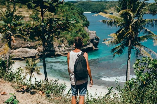 Jeune mec avec une barbe et un sac à dos posant dans la jungle dans un bonnet Photo gratuit