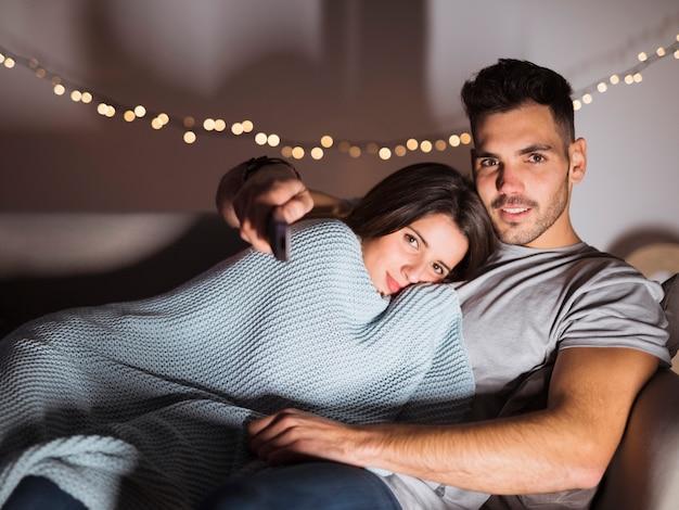 Jeune mec avec dame étreignant tv à distance et couché sur le canapé Photo gratuit