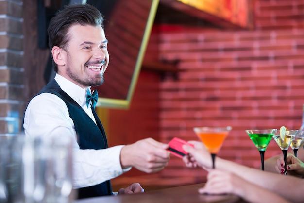 Un jeune mec donne un cocktail à toutes les filles. Photo Premium