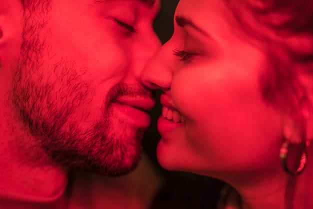 Jeune mec positif embrasser dame souriante en rougeurs Photo gratuit