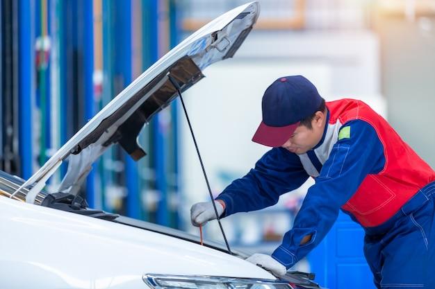 Un jeune mécanicien automobile dans un centre de réparation automobile analyse des problèmes de moteur et les vérifie. mécanicien automobile travaillant dans un centre de service de réparation automobile. Photo Premium