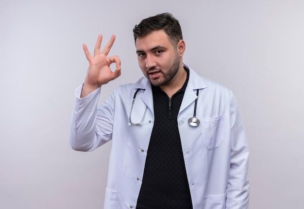Jeune Médecin De Sexe Masculin Barbu Portant Blouse Blanche Avec Stéthoscope Souriant Faisant Signe Ok Sur Fond Blanc Photo gratuit