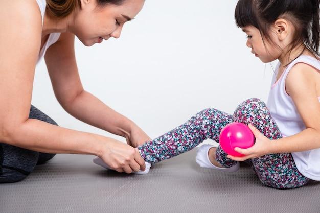 Jeune mère aide fille mignonne portant des chaussures Photo gratuit