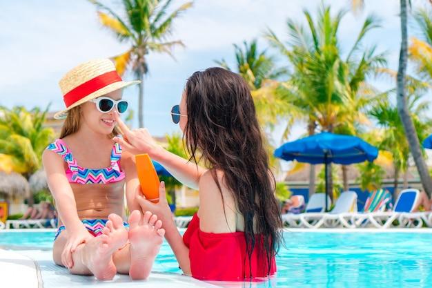 Jeune mère, appliquer, crème soleil, à, nez nez, dans, piscine Photo Premium