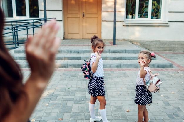 Jeune mère faisant signe à ses filles avant les cours à l'école primaire en plein air. Photo Premium