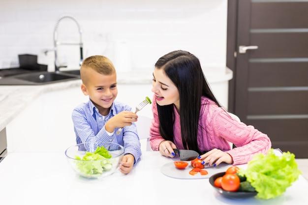 Jeune Mère Avec Fils Garçon Cuisine Salade Maman En Tranches Légumes Légumes Fils Donner à La Mère Dégustation De Salade. Famille Heureuse, Cuisiner, Nourriture, Jouissance, Style De Vie, Cuisine Photo gratuit