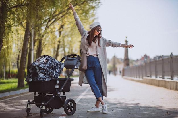 Jeune, mère, marche, voiture bébé, dans parc Photo gratuit