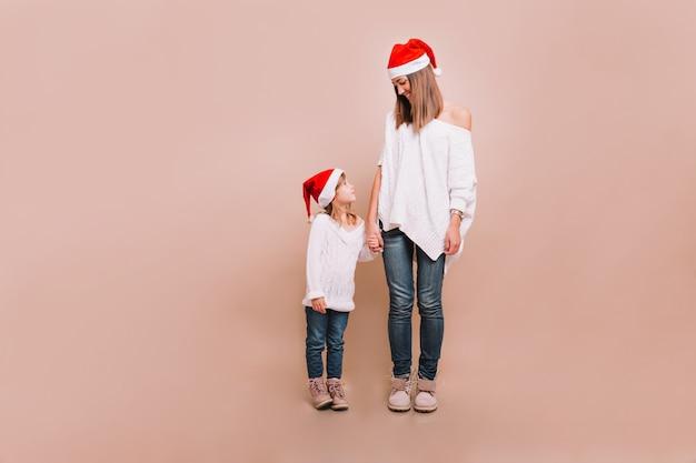 Jeune Mère Avec Petite Jolie Fille Debout Sur Un Mur Beige Portant Des Pulls Blancs Et Des Casquettes Du Père Noël à La Recherche De L'autre Et Se Tenant à La Main Photo gratuit