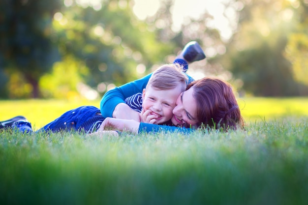 Jeune mère avec son fils, allongée sur une herbe dans le parc et embrasse joyeusement Photo Premium