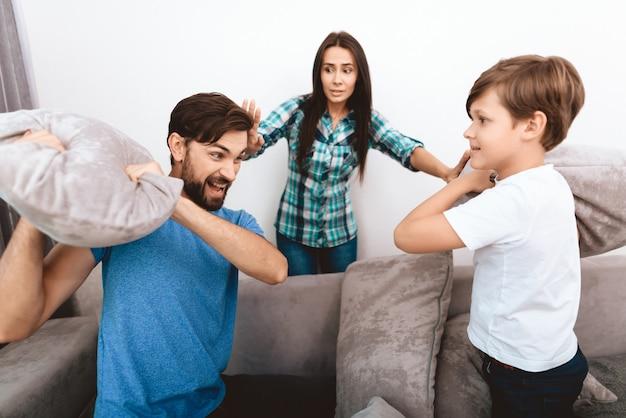 Jeune mère tente de calmer son mari et son fils adultes. Photo Premium