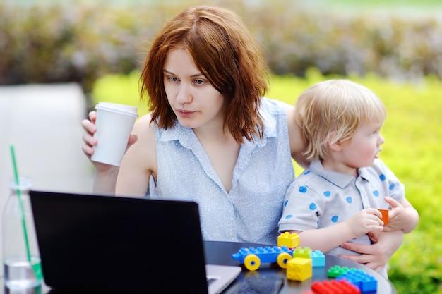 Jeune mère travaillant son ordinateur portable et tenant son fils triste de bambin Photo Premium