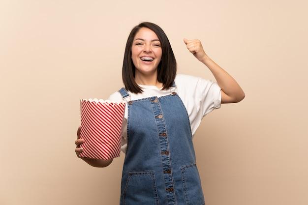 Jeune, mexicain, femme, isolé, mur, tenue, bol, pop-corn Photo Premium