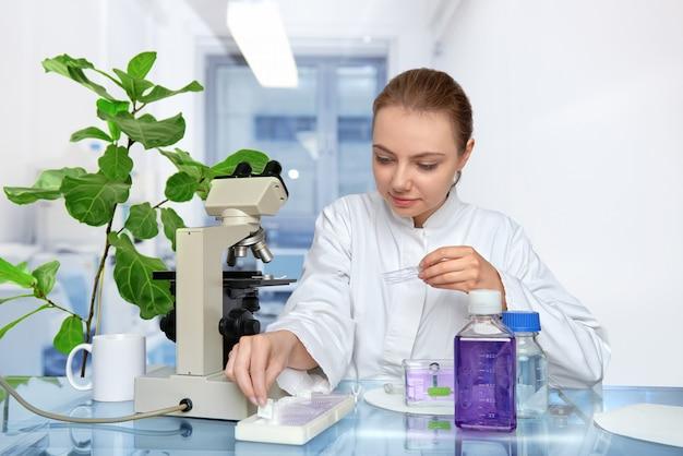 Une jeune microscopiste en blouse blanche sélectionne un échantillon de tissu pour microscopyspace Photo Premium