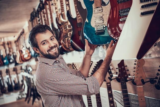 Jeune musicien barbu achète une guitare électrique dans un magasin de musique Photo Premium