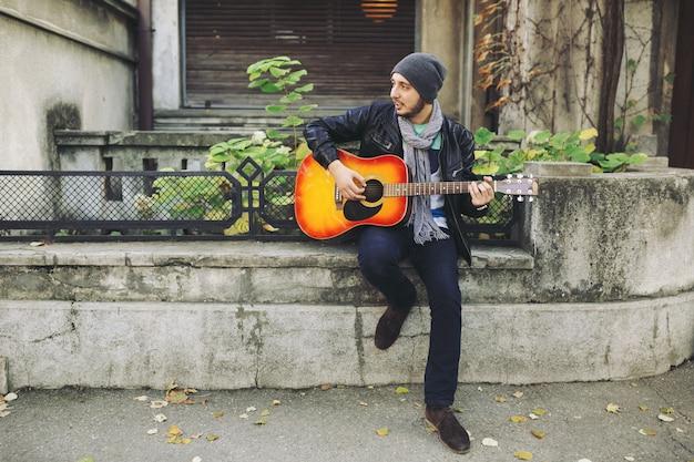 Jeune Musicien Avec Guitare En Ville Photo gratuit