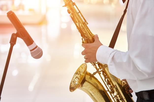 Jeune musicien de jazz joue du saxophone dans une grande salle Photo Premium