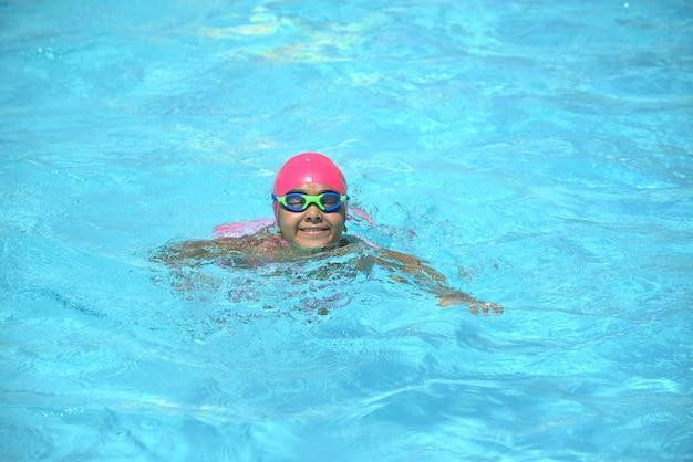 Jeune nageur, fille nageant dans l'eau de la piscine bleue Photo Premium