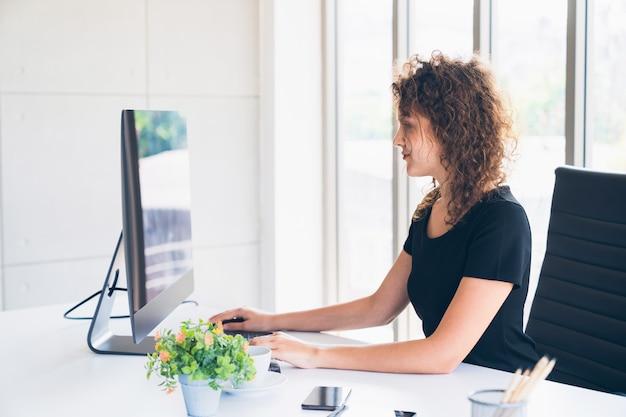 Jeune ouvrier créatif caucasien travaillant sur ordinateur de bureau à la maison Photo Premium