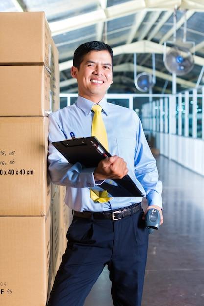 Jeune ouvrier indonésien en entrepôt avec scanner Photo Premium