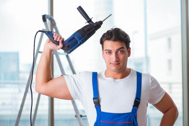 Jeune ouvrier avec perceuse à main Photo Premium