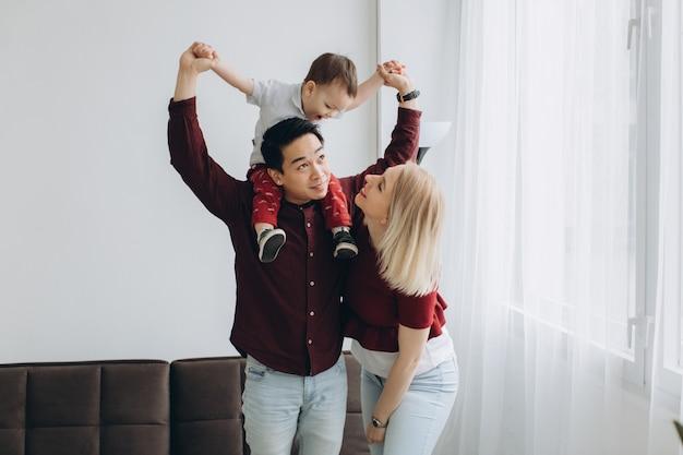 Jeune Papa Asiatique Et Maman Blonde Européenne Tiennent Son Fils Dans Ses Bras Dans Une Pièce Lumineuse. Concept Branché Multiculturel Photo Premium