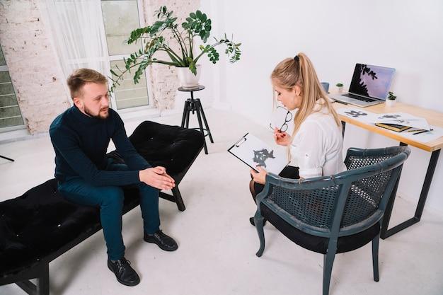 Jeune patiente en regardant une tache encrée de rorschach avec un psychologue au bureau Photo gratuit