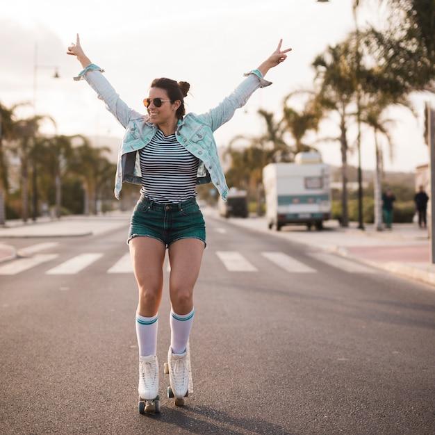 Jeune patineuse levant les bras en faisant le geste de la paix en équilibre sur la route Photo gratuit