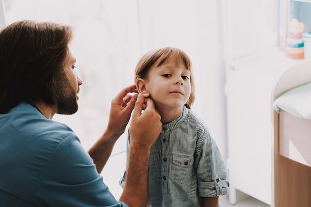 Jeune pédiatre examinant l'oreille de l'enfant en clinique Photo Premium