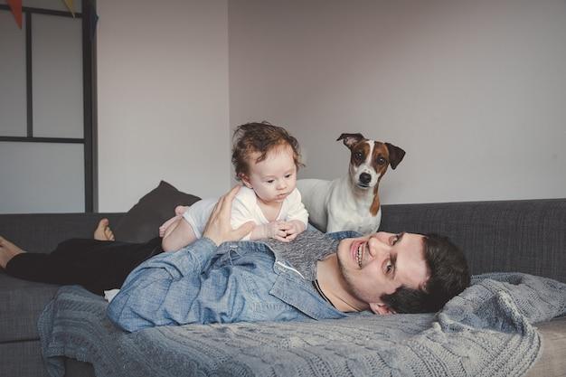Jeune Père Et Bébé Garçon à L'intérieur De La Maison Avec Chien Photo Premium