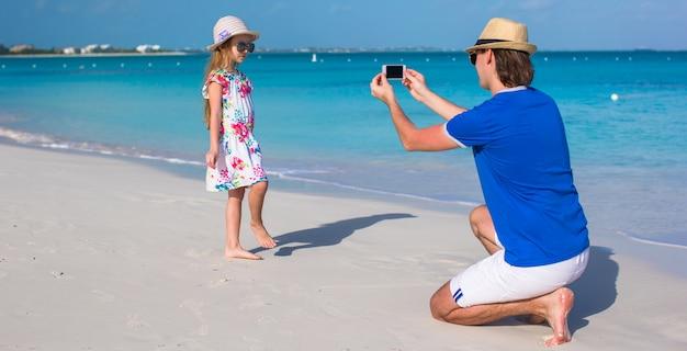 Jeune père en photo sur le téléphone d'une fille à la plage Photo Premium