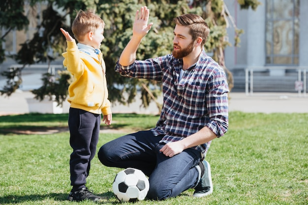 Jeune Père Et Son Petit Fils Donnant Cinq Haut Photo gratuit