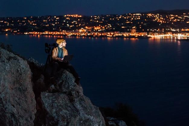 Jeune photographe de rêve assis sur un précipice et travaillant sur un ordinateur portable avec vue sur la mer et les montagnes Photo Premium