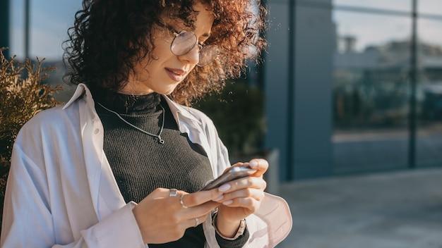 Jeune Pigiste Aux Cheveux Bouclés Discutant Avec Quelqu'un à L'extérieur Tout En Portant Des Lunettes Dans Une Journée Ensoleillée Photo Premium