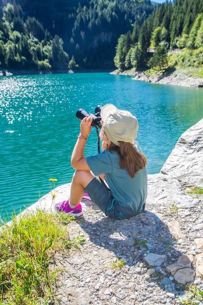 Jeune randonneur regarde le panorama avec le télescope Photo Premium