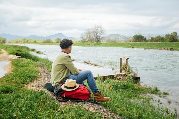 Jeune randonneur situé près de la belle rivière Photo gratuit