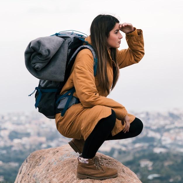 Jeune randonneuse assise au sommet d'un rocher avec son sac à dos qui protège les yeux Photo gratuit