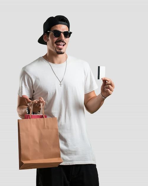 Jeune rappeur, souriant et souriant, très enthousiaste, tenant la nouvelle carte bancaire et ses sacs, prêt à faire les magasins Photo Premium