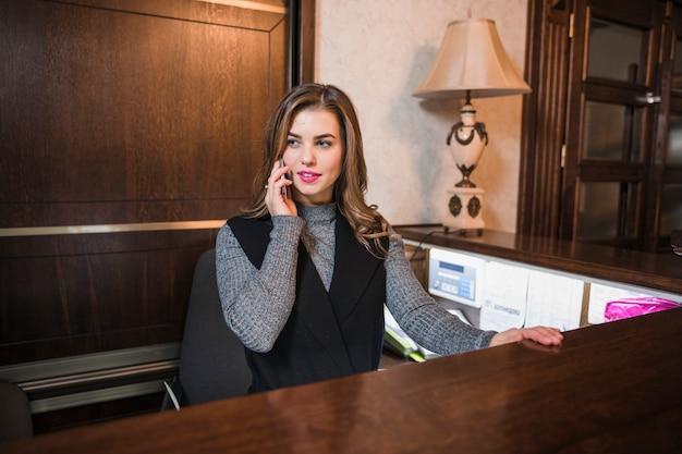 Jeune réceptionniste assis à son bureau parlant au téléphone mobile