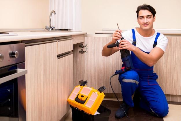 Jeune réparateur travaillant à la cuisine Photo Premium