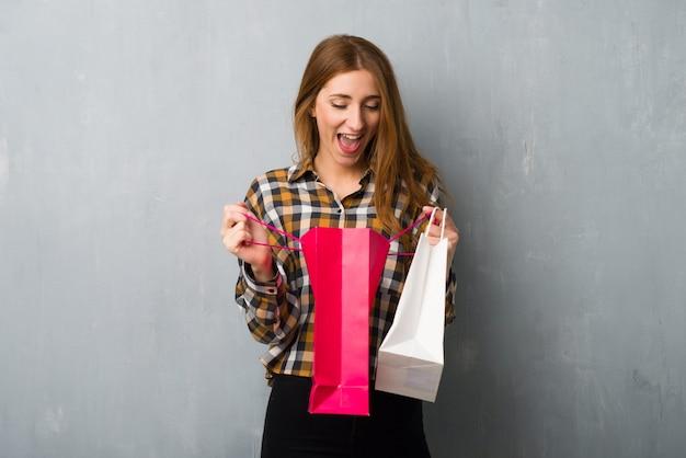 Jeune rousse sur le mur de grunge surpris tout en tenant beaucoup de sacs Photo Premium