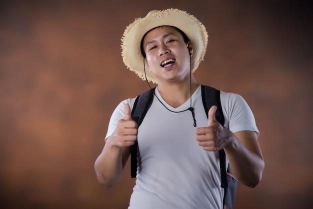 Jeune routard asiatique avec sac et chapeau Photo gratuit