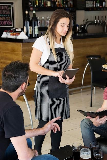 Jeune serveuse prenant commande sur tablette numérique au bar Photo gratuit