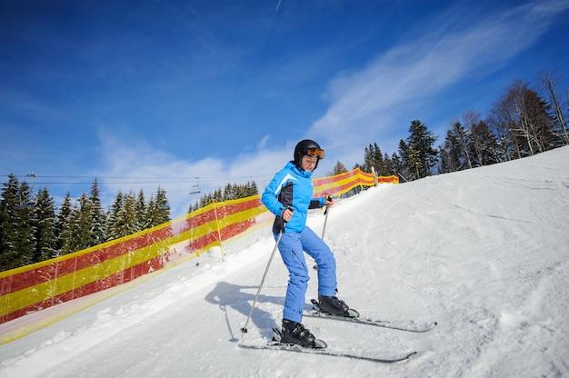 Jeune skieuse sur une journée ensoleillée à la station de ski Photo Premium