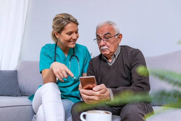 Jeune soignant montrant le vieil homme heureux comment utiliser un smartphone Photo Premium