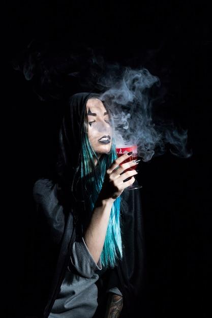 Jeune sorcière en capuche tenant un gobelet pourpre cramoisi Photo gratuit