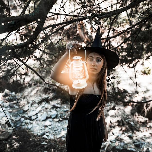 Jeune sorcière avec chemin éclairant la lampe dans la journée Photo gratuit