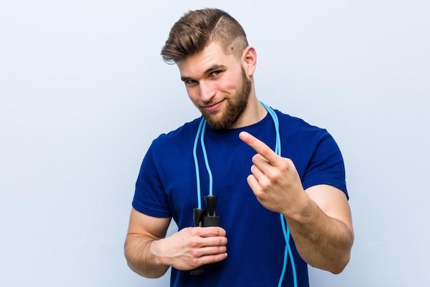 Jeune Sportif Caucasien Avec Une Corde à Sauter Pointant Avec Le Doigt Sur Vous Comme Si Vous Invitiez à Vous Rapprocher. Photo Premium