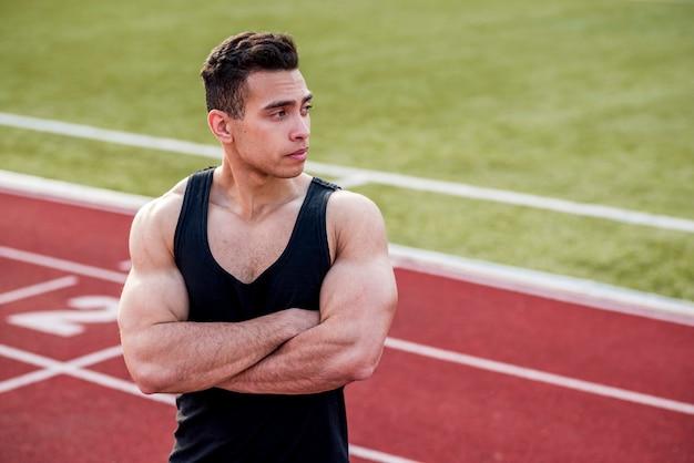 Jeune sportif musclé avec son bras croisé debout sur la piste de course Photo gratuit