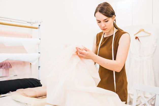 Jeune styliste en train de choisir le tissu en magasin Photo gratuit